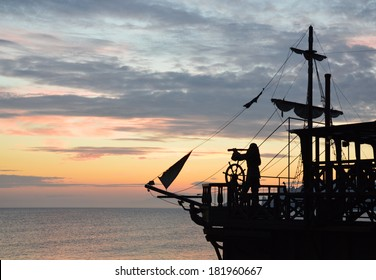 silhouette of a pirate ship with a captain behind steering wheel, looking through spyglass. (not an actual ship, imitation)