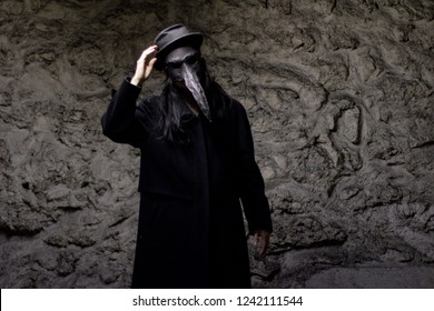 Silhouette of a plague doctor, all dressed in black, with the beak mask and long dark hair. One hand on the hat like a salute. Grey texture background behind