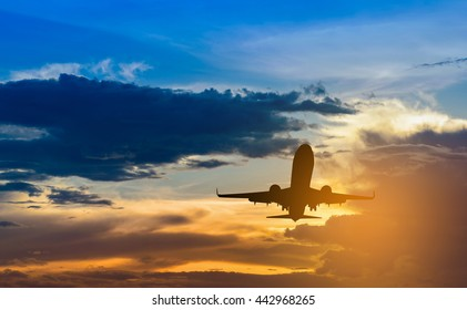 Silhouette of plane fly on sky during sunset.