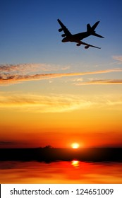 silhouette of plane fly over water during sunrise