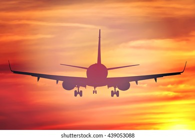 Silhouette of plane flying at beautiful colorful sunset. Nature. Flight. Vacation. Journey. Conceptual image.Toned colors