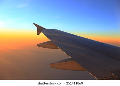 Silhouette of plane wing at beautiful sunset