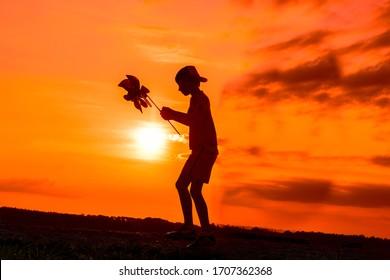 Silhouette des spielenden Jungen mit Windmühle in der Natur auf bewölktem Hintergrund