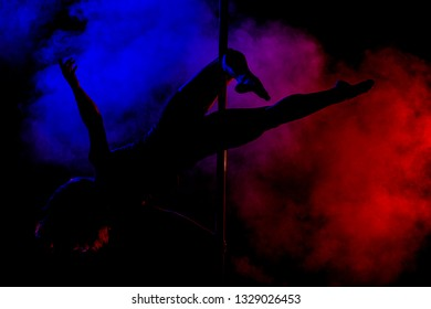 silhouette of a pole dance girl with red and blue smoke in the background