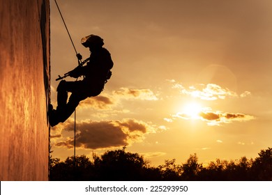 Silhouette of police officer during rope exercises with weapons