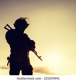 Silhouette of police officer with weapons at sunset