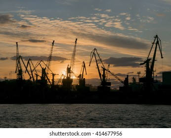 Silhouette of port cranes on sunset sky with colorful clouds  background