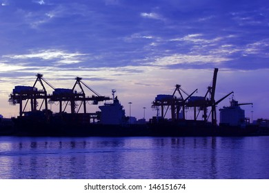 Silhouette of port warehouse with container cargo and crane bridge