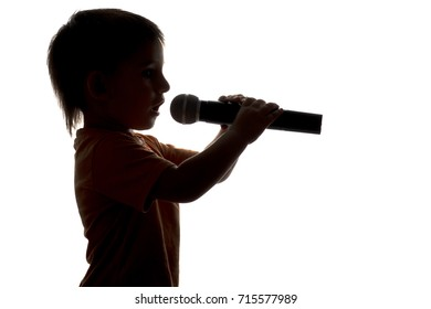 silhouette portrait of little child singing karaoke into microphone on white isolated background