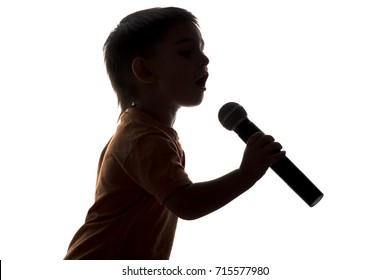 silhouette portrait of little happy boy singing into microphone on white isolated background