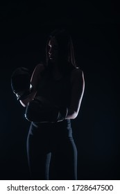 Silhouette portrait of a sexy fit woman posing in dark contrast with boxing gloves