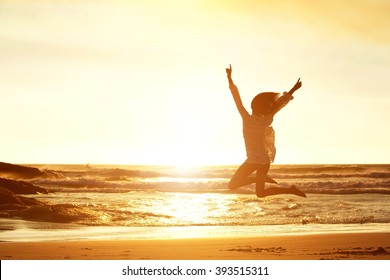 Silhouette portrait of young woman jumping for joy at beach during sunset