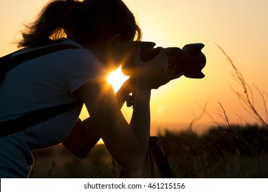 silhouette portrait of a young woman photographing a beautiful nature at sunset on photo equipment