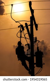 The silhouette of power lineman climbing on an electric pole with a transformer installed. And replacing the damaged hotline clamp, bail clamp, dropout and surge arrester that causes a power outage.