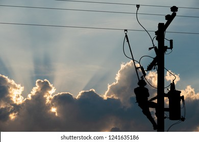 Silhouette, power lineman use clamp stick (insulated tool) to closing a transformer on energized high-voltage electric power lines. Isolated from background with clipping path.