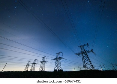 Silhouette of power lines on the background of beautiful starry sky at night.