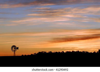 Silhouette of a power windmill at dawn in the Arizona desert