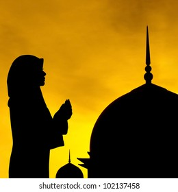 Silhouette of prayer and mosque in sunset.
