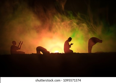 Silhouette of praying Muslim man on toned foggy background. Ramadan Kareem background. Muslim Eid holiday decoration. Praying people religion concept. Selective focus
