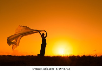 Silhouette of pregnant woman in a open field holding long flowing fabric blowing in the wind.