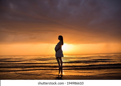 Silhouette of a pregnant woman  at sunset in sea