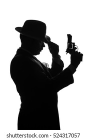 Silhouette of a private detective with a gun in right hand. Gangster looks like mafiosi Al Capone and stay side to camera. Police criminal scene in black and white. Isolated or cutout