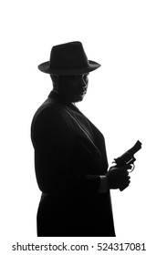 Silhouette of a private detective with a gun in right hand. Gangster looks like mafiosi Al Capone. He wears mob jacket. Police criminal scene. Studio shot isolated or cutout from background