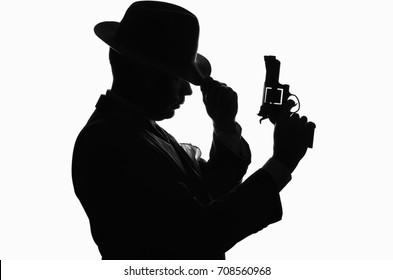 Silhouette of private detective with a gun in right hand. Criminal scene. Studio shot