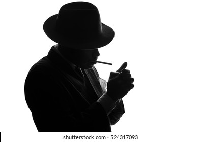 Silhouette of private detective in old fashion hat lights a cigarette. Gangster looks like mafiosi Al Capone and stay side to camera. Police criminal scene in black and white. Isolated or cutout