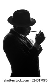 Silhouette of private detective in old fashion hat lights a cigarette. Gangster looks like mafiosi Al Capone and stay side to camera. Police criminal scene in black and white. Isolated from background