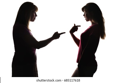 The silhouette of problematic relations in the family between mother and teenager, family quarrel, mom pokes finger, blaming, scolds and chastising young daughter on white isolated background