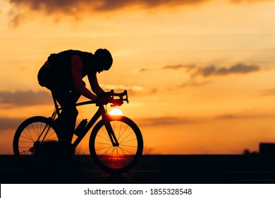 Silhouette of professional cyclist in protective helmet using bike for sport activity on paved road. Background of summer sunset.