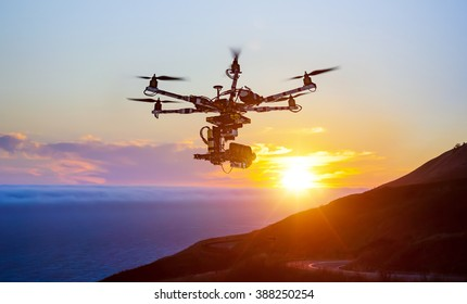 Silhouette of the professional drone with cinema camera hovering in the summer sunset.