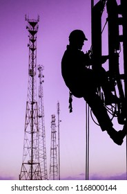 Silhouette of professional industrial climber in helmet and uniform works at height for instaling communication equipment and antenna and telecommunication towers with sunset sky as background. Risky
