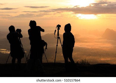 silhouette of professional photographer on the top mountain looking to sunrise view in the morning. the concept of looking to Sea Fog and mountain view.