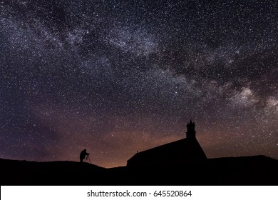 Silhouette of Professional photographer taking Night stars picture over Pointe du Van church in Brittany, France.