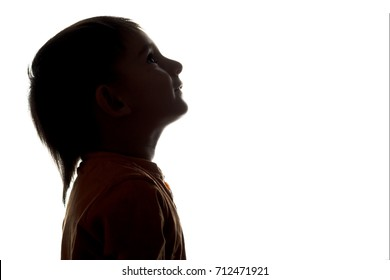 silhouette profile of the face of a little boy looking upwards on a white isolated background