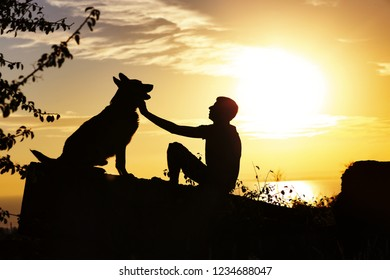 silhouette profile of man and dog sitting in front of each other on nature, boy caress his pet at sunset in a field, concept friendship animal and human