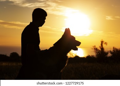 silhouette profile of a young man with a dog enjoying beautiful sunset in a field, boy fondle his favorite pet on nature, concept friendship of animal and human