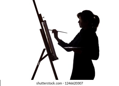 Silhouette profile of a young woman painting a picture on an easel on a white isolated background, the figure of a girl with a brush and a palette of colors , a concept of hobby and creative
