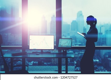 Silhouette of prosperous business person standing near panoramic office window with city view. Earning on stock exchange, financial market. Female economist near desktop with PC computer with graphs