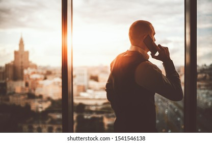 Silhouette of a prosperous man entrepreneur standing near the panoramic window of a luxurious business office skyscraper and pensively looking on an evening cityscape while talking on the phone