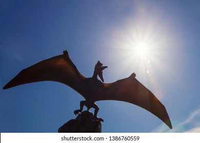 Silhouette of a pterosaur with sun and sky