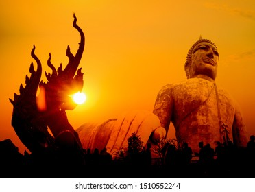 Silhouette public big glod Buddha, sunset in Thailand, Yellow-gold Buddha and golden orange background and naka.