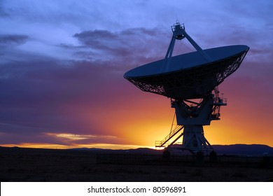 Silhouette of a radio telescope at the Very Large Array (VLA) in New Mexico, USA, at sunset