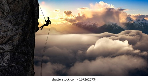 Silhouette Rappelling from Cliff. Beautiful aerial view of the mountains during a colorful and vibrant sunset or sunrise. Landscape taken in British Columbia, Canada. composite. Concept: Adventure
