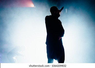 Silhouette of the rapper on the stage. Bright stage light and smoke in the background.