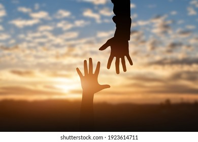 Silhouette of reaching, giving a helping hand, hope and support each other over sunset background. Help concept