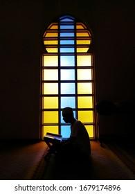Silhouette des Lesens quran.Junge muslimische Mann lesen quran Hintergrund.