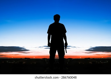 silhouette rear of man standing hand hold holding gun revolvers on sunrise in the city background